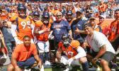 The defensive line group — Derek Wolfe (95), Shelby Harris (96), Zach Kerr (92), Domata Peko Sr. (94), Kyle Peko (90), DeMarcus Walker (57) and Adam Gotsis (99) — take a group photo with Peko Sr.'s father