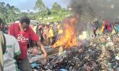 A photo taken on February 6, 2013 shows a crowd watching as a young mother accused of sorcery, is stripped naked, reportedly tortured with a branding iron, tied up, splashed with fuel and set alight on a pile of rubbish topped with car tyres, in Mount Hagen city in the Western Highlands of Papua New Guinea. [Photo: AFP / Post Courier via RNZI]