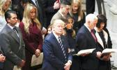 In this Jan. 21, 2017, file photo, President Donald Trump, center, accompanied by first lady Melania Trump, third from right, Vice President Mike Pence, second from right, and his wife Karen, right, and the Trump family, glances towards the balcony during a National Prayer Service at the National Cathedral, in Washington. Some websites published false stories in April 2017 claiming Trump and Pence consoled Jehovah's Witnesses by praying with them after Russia banned the religion's members from operating an