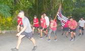 Members of the community march to honor fallen firefighters