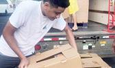 Ā'oga Samoa boys unloading cartons of food