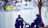 Homeland security personnel siting on shore in sight of yacht