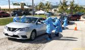 Car at a Covid-19 testing point in Guam with medical people standing by.