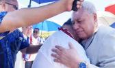 Tuila'epa Sa'ilele Malielegaoi in the arms of the Head of State