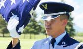 Senior Airman Darias Faaita preparing to present an American Flag to its recipient.