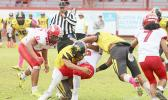Faga'itua Vikings ball carrier Roy Ulugalu is tackled by two Nu'uuli Wildcat defenders
