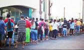 A crowd of people seen standing in line outside of the Territorial Bank of American Samoa (TBAS) waiting for the bank to open so they could cash their stimulus checks
