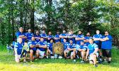 the Manu Bears rugby team, shows team officials and players posing for a photo