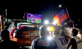 Car club, Leai Sou Feau members watch game on a big screen TV in front of the Government building.