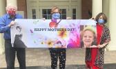 Three siblings wearing cloth face masks with a Happy Mother's Day sign
