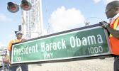 """In this Thursday, Dec. 17, 2015 file photo, Dale Moncur, left, and Cedric Anderson of Palm Beach County Traffic Operations, hold a sign for the new President Barack Obama Highway in preparation to change it from the """"Old Dixie Highway"""" in Riviera Beach, Fla. On Friday, Jan. 5, 2018, The Associated Press reported that stories circulating on the internet about President Donald Trump ordering the name of the highway changed back to """"Old Dixie"""" are untrue. (Lannis Waters/Palm Beach Post via AP)"""