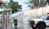 Firemen spraying water on storage tanks