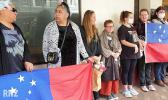 A protest over the cartoon in Dunedin with people holding flags.