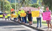 A group of about 15 peaceful protesters on the sidewalk in front of Utulei Beach
