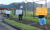 Three protesters with signs protesting governer's checks to fono