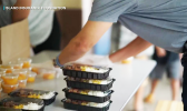 Man stacks meals in containers