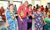 Evelyn Lili'o Satele (left) helps escort an elderly member of the community
