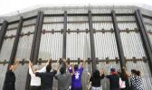 In this July 14, 2013, file photo, pastors and others raise their arms on the San Diego side of a border fence during a cross-border Sunday religious service with others on the Tijuana, Mexico side of the fence. The AP reported Sept. 8, 2017, that a story claiming Congress had approved President Donald Trump's request for $1.6 billion in border wall funding is false. (AP Photo/ Gregory Bull, File)