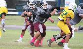 Warriors offensive lineman Marvin Atuatasi opening a huge gap for Panapa Filoiali'i at midfield, during the opening half of their varsity match against the Lions last Friday evening – Tafuna shut out Leone and claimed victory in their 38 point win.  [photo: TG]